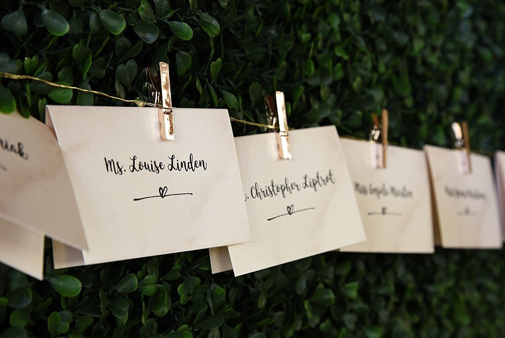 Place cards hanging on a gold wire string in front of a lush green wall | Vintage Garden Wedding at the Historic Alfred I DuPont Building in Miami, FL