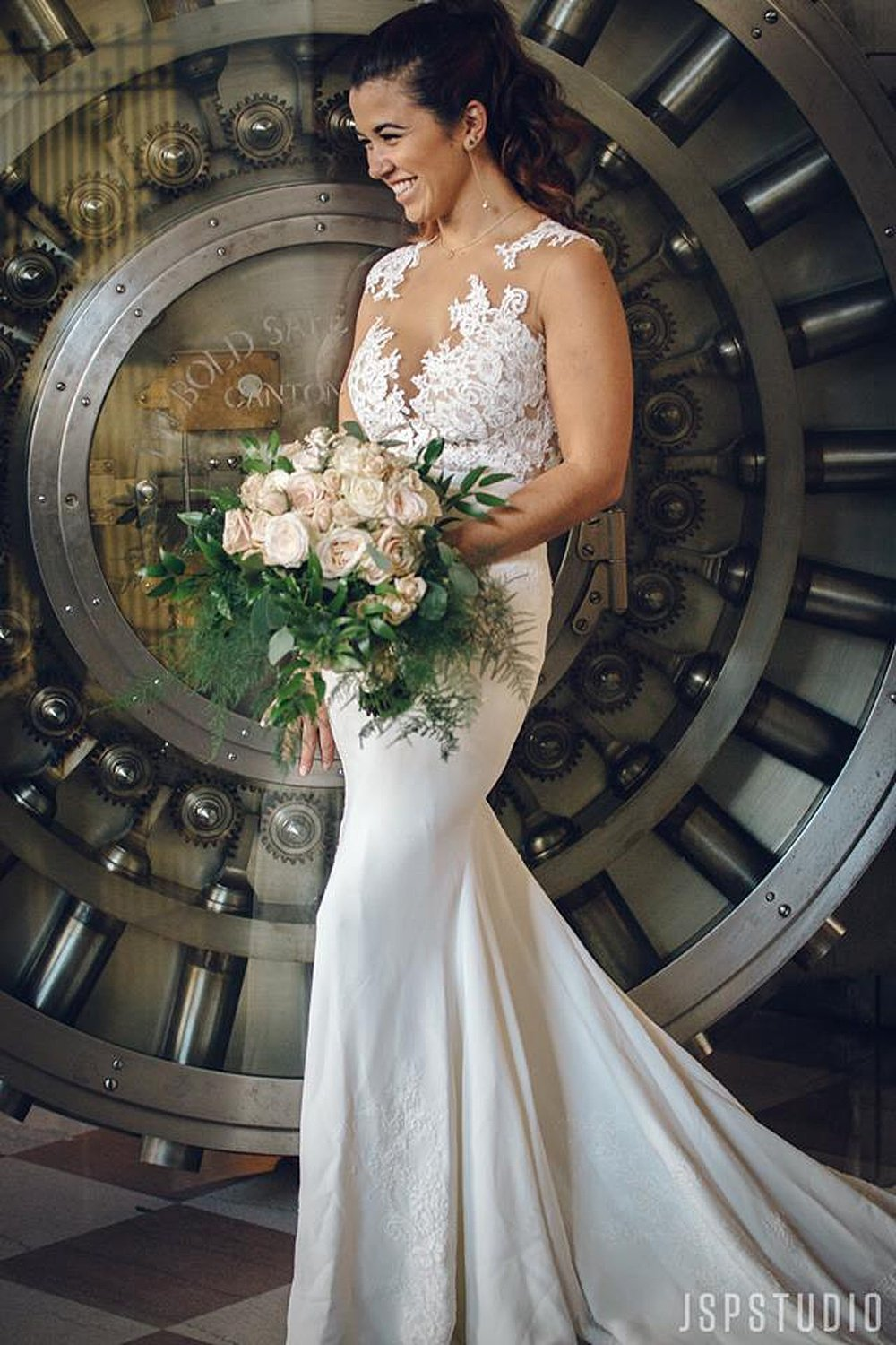 Beautiful Bride in Lace Gown in front of the infamous vault door at the Historic Alfred I Dupont Building